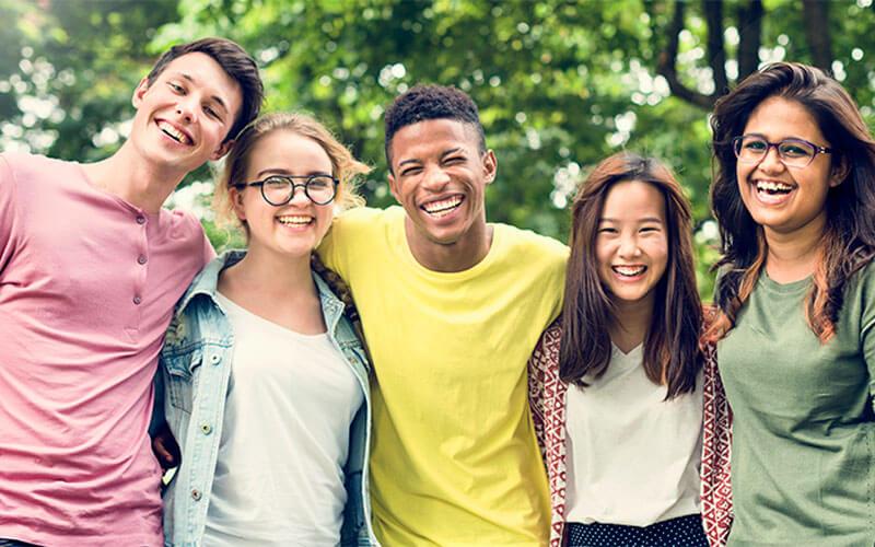 Group of five teenage friends stand shoulder to shoulder smiling