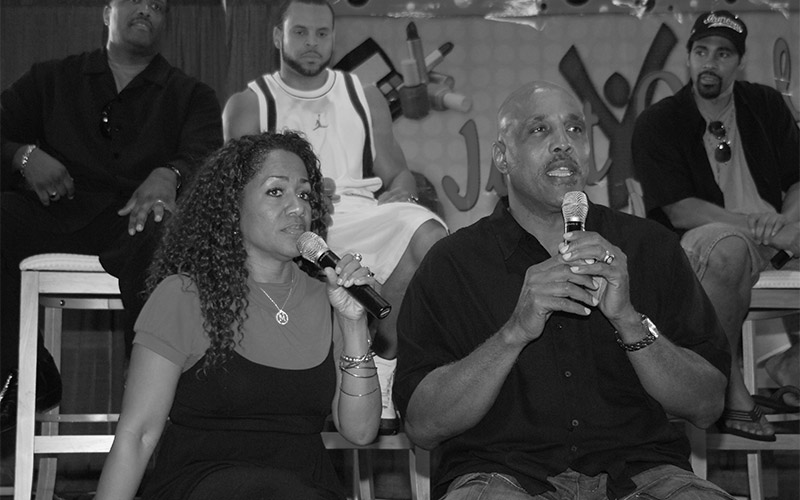 Gail Moore (left) and Art moore (right) sit on stage holding microphones, black and white image