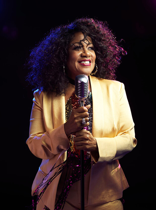 Gail Moore in gold suit holing vintage microphone