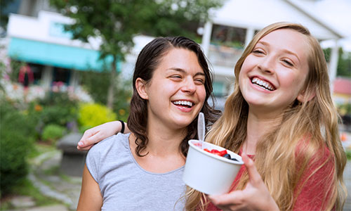 Two young girls hug and laugh while holding yogurt