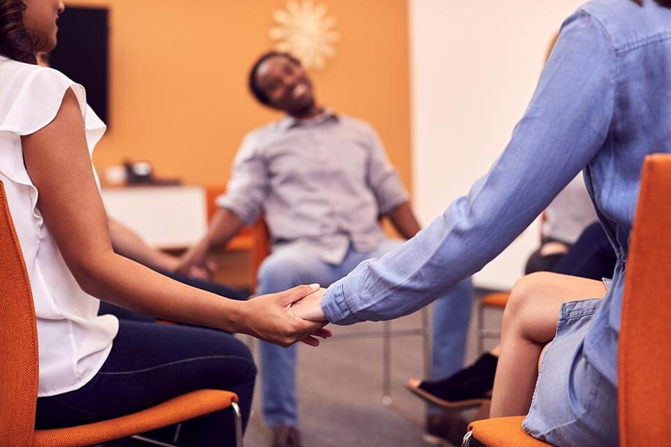 Group sitting in circle hold hands