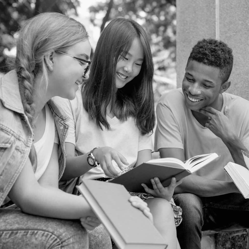 Three teens holding books study out side, black and white image